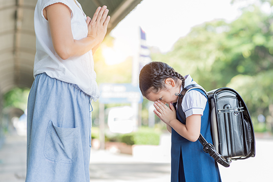 Child showing respect to teacher